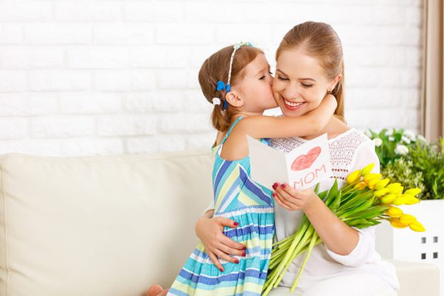 Mother reading a handmade card and bouquet of tulips while young daughter kisses her on the cheek.