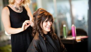 Hairstylist finishing curling her clients' hair. Client is smiling and happy.