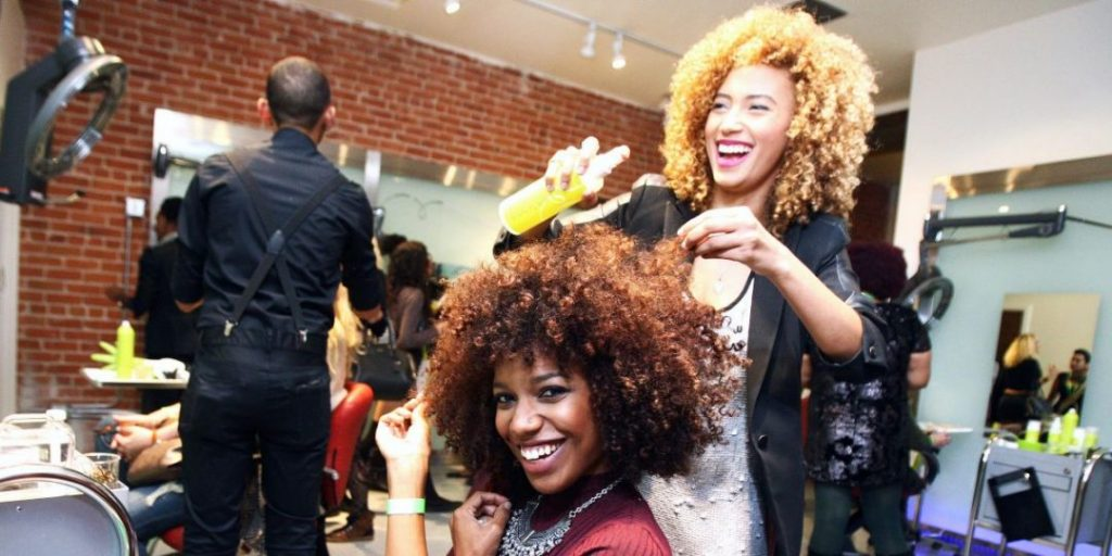 Hair stylist laughing with her client.