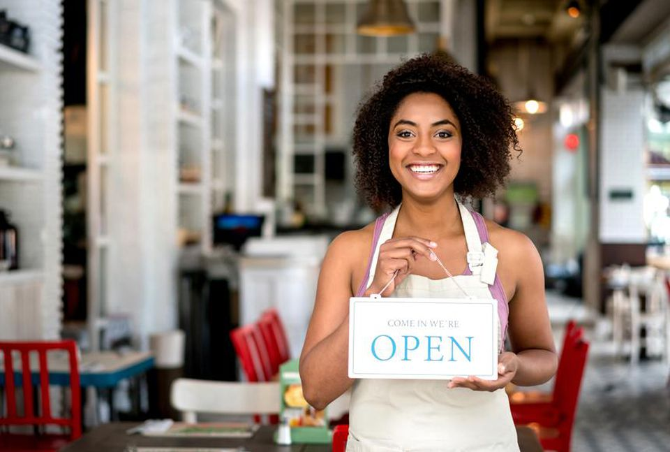"""Woman holding an """"open"""" sign"""