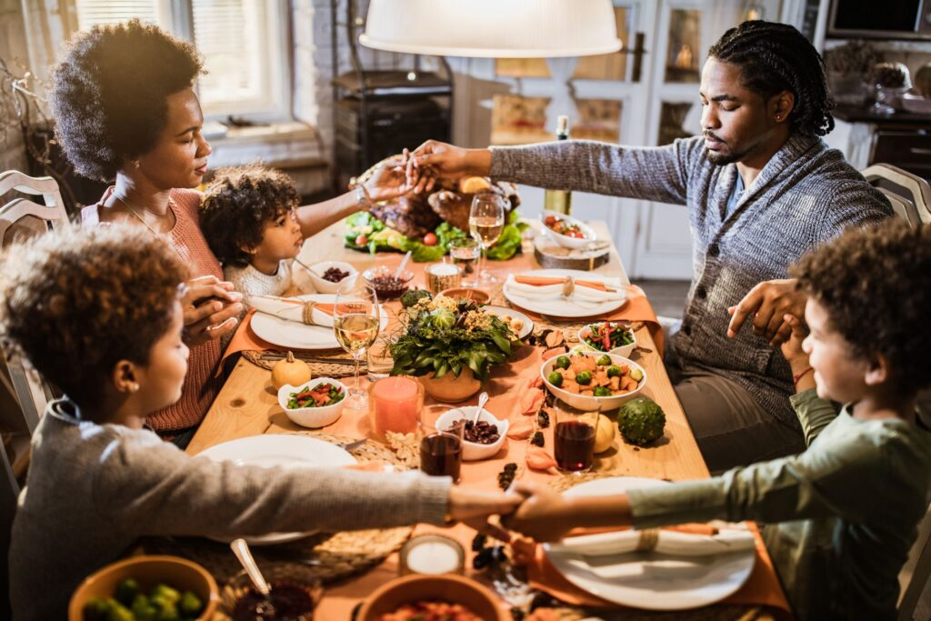 Family sitting around a table showing thankfulness and gratitude as they pray over the food.