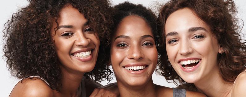 3 women smiling with natural makeup.