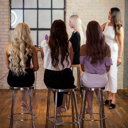 Women learning how to put in hair extensions through continuing education.