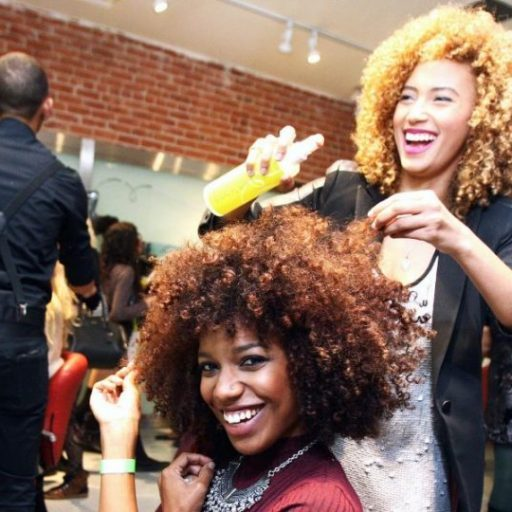 A photo of a hairstylist spraying finishing product into her clients hair while both are laughing.
