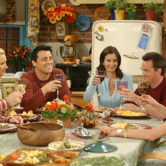 The cast of Friends acting out Thanksgiving dinner.